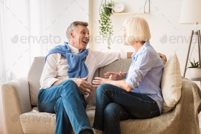 Happy senior spouses talking, enjoying conversation and joking