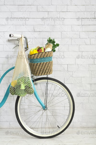 Retro bicycle with net shopping bag full of fresh vegetables