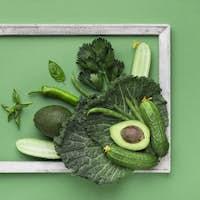 Composition of fresh green vegetables inside wooden frame