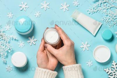 Woman using winter cream on blue