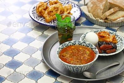 moroccan ramadan iftar meal, harira soup, chebakia, dates, mint tea and khubz