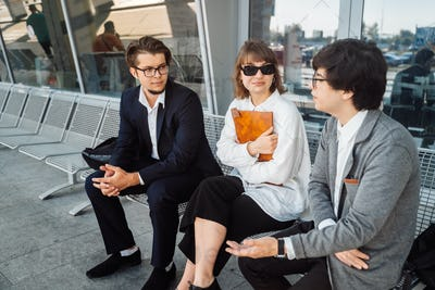 Two businessmen and a secretary discuss an important issue outside