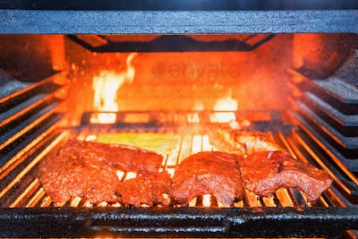 Grilling pork ribs in stove close up