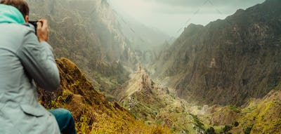 Rear view of traveler making photo of amazing steep mountainous terrain with lush canyon valley on