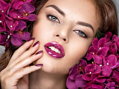 woman with purple make-up of lips and fingernails