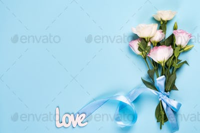Minimal composition with a Eustoma flowers on pink background, top view. Love greeting card