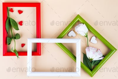 Empty frame and flowers flat lay on beige paper background with copy space. Holiday concept