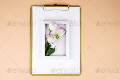 Clipboard with eustoma flower and white frame on beige paper background, flat lay. Post card mockup