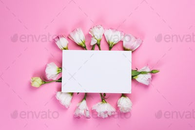Paper sheet made of eustoma flower on pink background, flat lay. Floral decorative card