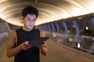 Portrait of young handsome Asian man using digital tablet outdoors at night