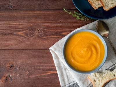 Dietary vegetarian pupmkin cream soup puree,  on dark brown wooden table, top view, copy space.