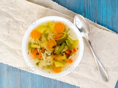 Bright spring vegetable dietary vegetarian soup, linen napkin, top view, blue background.