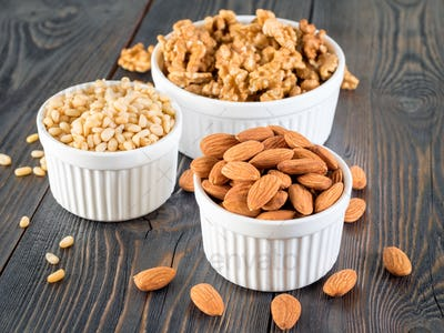 assorted nuts in white bowl on wooden dark background, mix of walnuts, almonds and cedar, side view