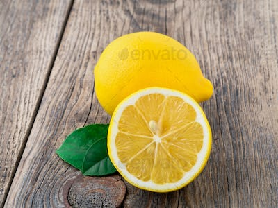 fresh lemon and cut off half on wooden old table, side view
