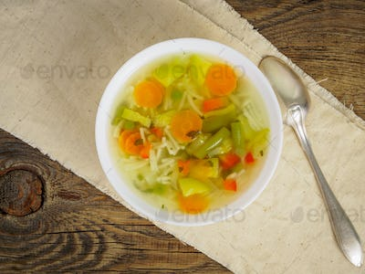 Bright spring vegetable dietary vegetarian soup, linen napkin, top view, wooden background.