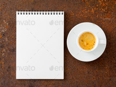 blank sheet of notebook with a spiral and cup of coffee on rusted old iron table, top view.