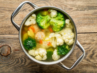 large metal pan with delicious hot soup of vegetables and meatballs