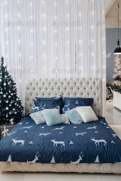 Tidy bed with Christmas tree and garland