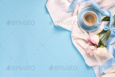 Having a cup of coffee , flowers eustoma on blanket on a blue background, flat lay copy space