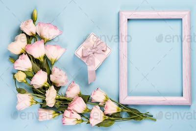 Empty white frame, present box and flowers eustoma on blue paper background with copy space. Flat