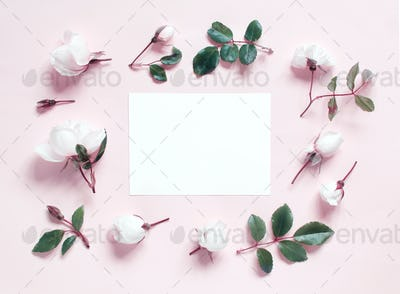 Flowers and paper on a light pink background