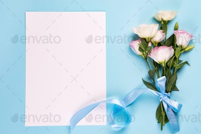 Eustoma flowers with paper sheet on a blue background, top view. Valentines day, birthday, mother or