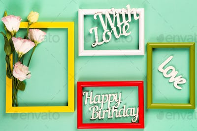 Colorful picture or photo frames with flowers and letters on a green paper background. Copy space