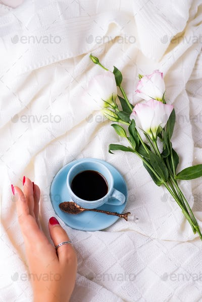 A tray with a cup of coffee, gift box, flowers and rings with hand on the bed. Valentine's Day