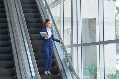 Business woman on escalator