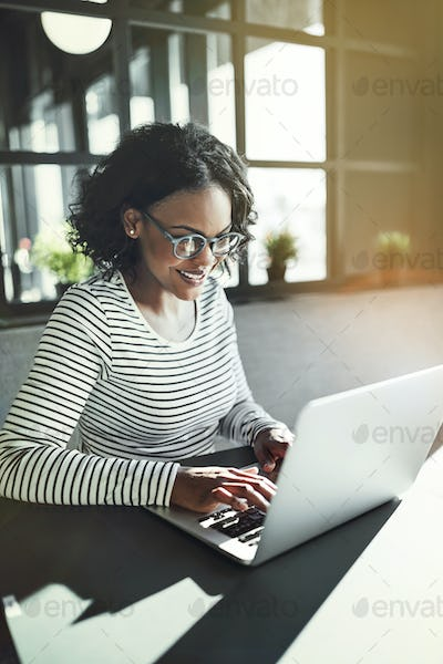 Smiling young African woman working with a laptop