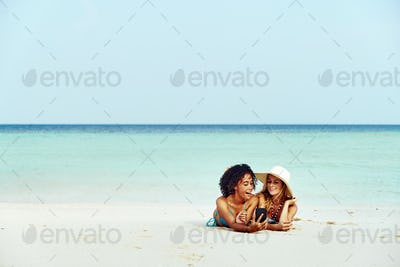 Friends in bikinis taking selifes while suntanning on a beach
