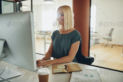 Smiling businesswoman working at her office desk in the afternoon