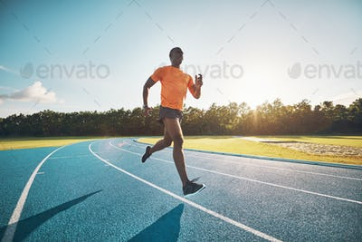 Focused young athlete sprinting alone down a running track