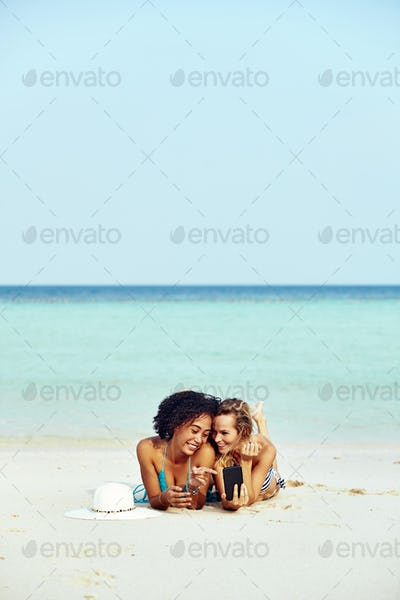 Two suntanning friends looking at cellphone photos on a beach