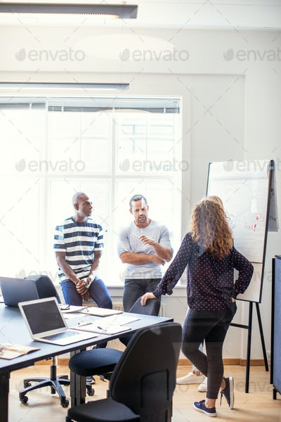 Coworkers talking together in an office after a meeting