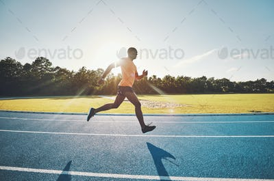 Lone athlete sprinting along a track on a sunny day