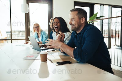 Businessman laughing with a group of office colleagues at work