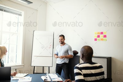 Smiling manager talking with staff during a whiteboard presentation