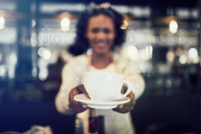 Cafe barista offering up a cup of cfresh coffee