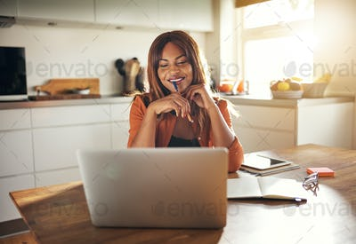Young entrepreneur working online at her kitchen table at home