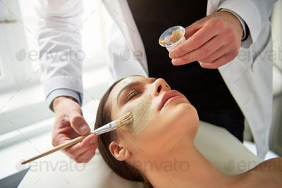 Woman lying with eyes closed while cosmetologist putting mask