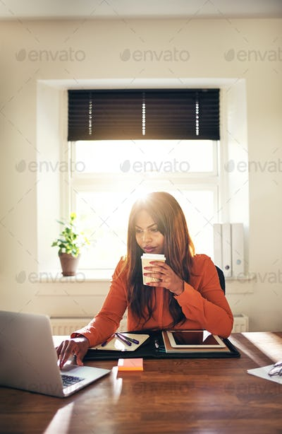 Young female entrepreneur working online at home drinking coffee