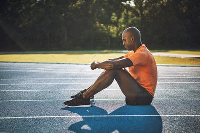 Focused young runner sitting alone on a track