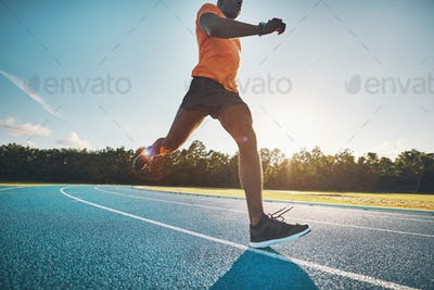 Fit young African athlete running alone on a track