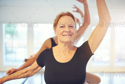 Mature smiling woman standing with hand up in ballet class