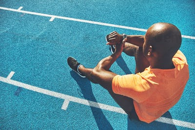Young runner sitting on a track checking his lap time