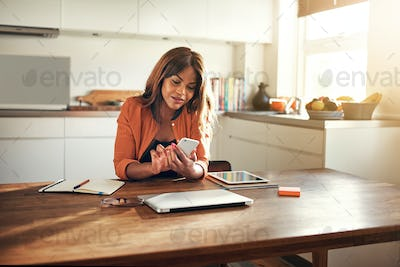 Smiling young entrepreneur reading messages while working in her kitchen