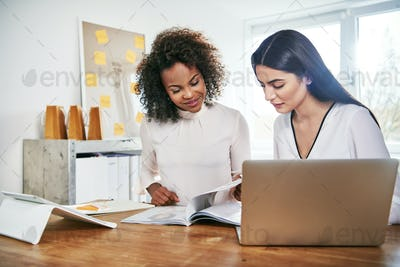 Two young business partners working on paperwork