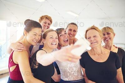 Group of smiling women taking selfies in a dance studio