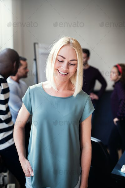 Smiling designer standing in an office with colleagues behind her